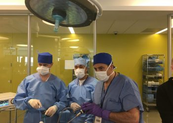 Group of surgeons looking at a screen with scrubs and masks on.